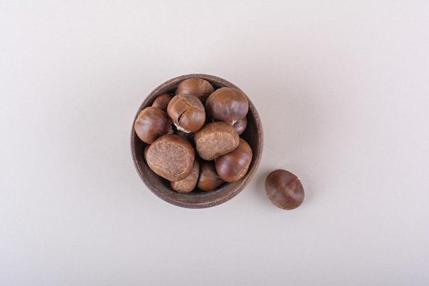 白い背景の上の有機乾燥栗の木のボウル。高品質の写真