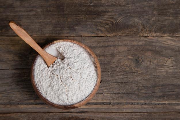 木製の表面に置かれた有機小麦粉の木製のボウル。高品質の写真
