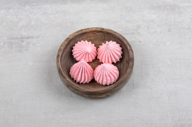 돌 테이블에 핑크 머 랭 과자 나무 그릇. 무료 사진
