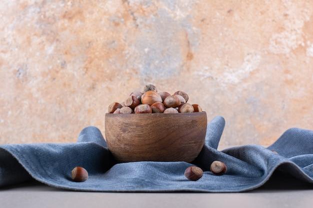 파란색 천으로 벗겨진 된 유기 hazelnuts의 나무 그릇. 고품질 사진