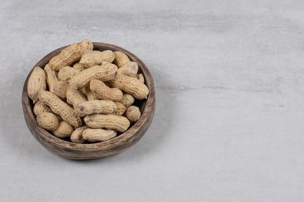 Деревянная чаша очищенного арахиса на мраморном фоне.