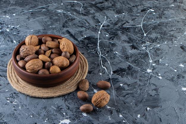 Деревянная чаша очищенных различных орехов на мраморной поверхности.