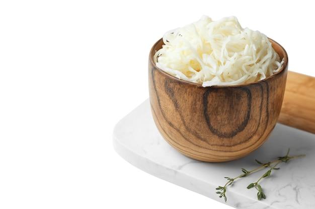 Деревянная миска вкусной квашеной капусты на белом столе. место для текста