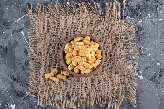 대리석 테이블에 맛있는 소금에 절인 크래커의 나무 그릇.