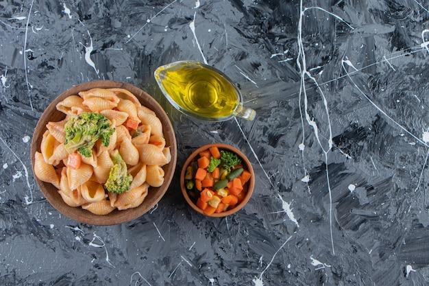 대리석 표면에 신선한 샐러드와 함께 맛있는 조개 파스타의 나무 그릇.