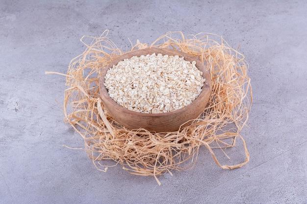 Деревянная чаша на кучу соломы, наполненная кучей овса на мраморном фоне. фото высокого качества