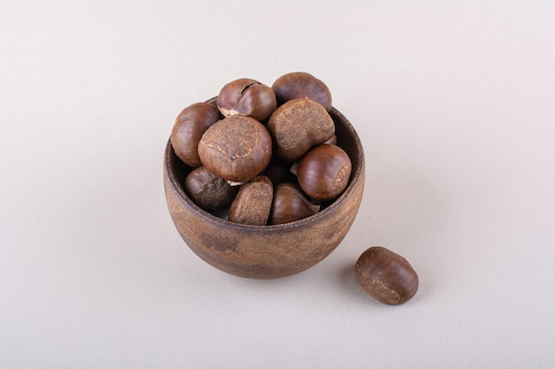 Wooden bowl of organic dry chestnuts on white background. high quality photo