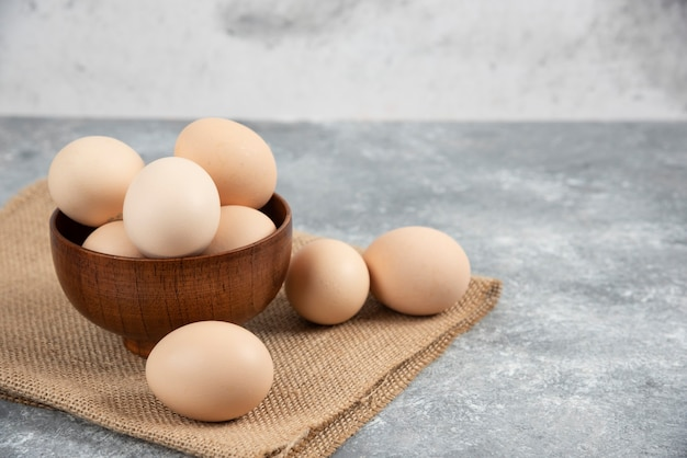 Wooden bowl of organic raw eggs on marble surface.