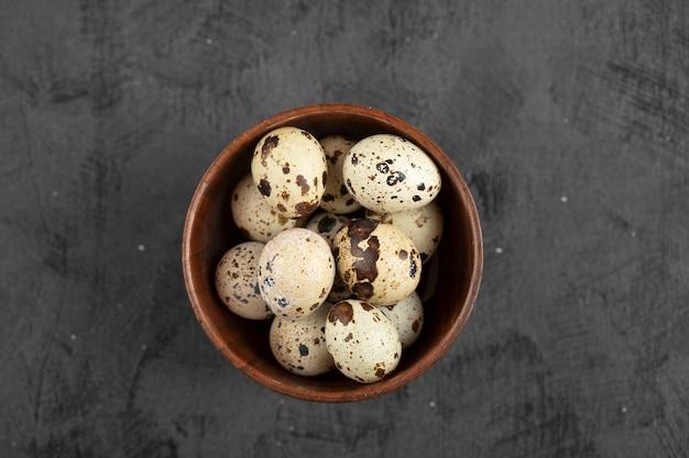 Wooden bowl of organic raw quail eggs on black surface.