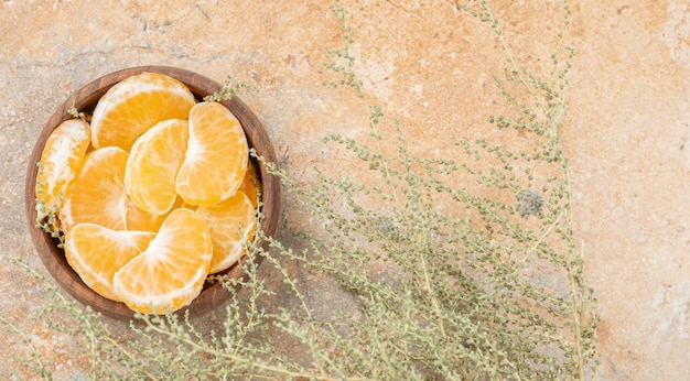 A wooden bowl of peeled tangerine on a stone surface