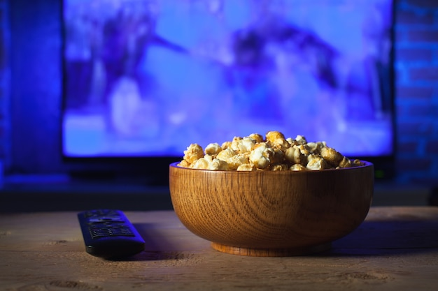A wooden bowl of popcorn and remote control.