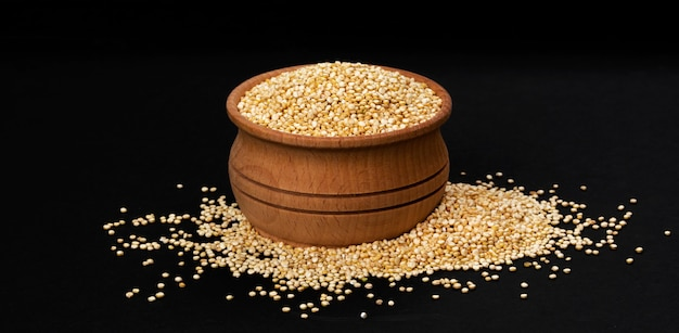 Wooden bowl of quinoa seeds isolated on black background, close up