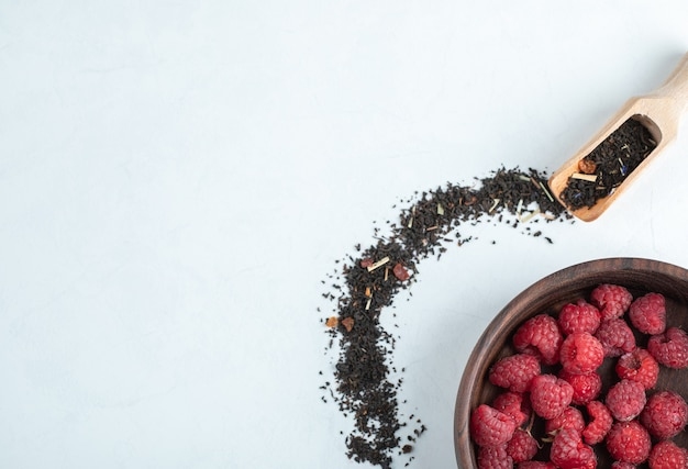 Wooden bowl of raspberries with spoon of black dry tea on stone