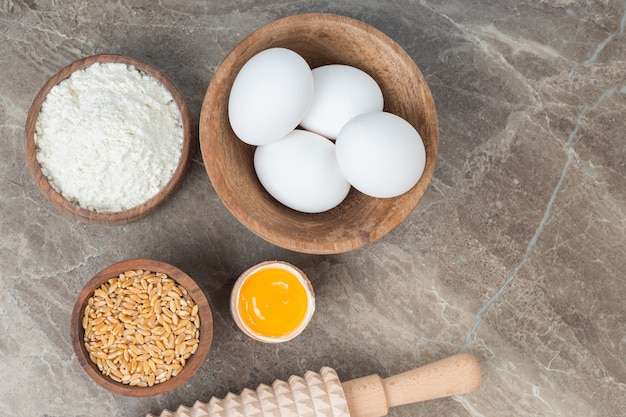 Wooden bowl of raw eggs, flour and barley on marble surface.