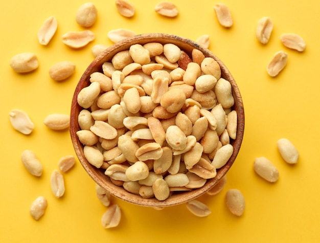 Wooden bowl of roasted salted peanuts on yellow background, top view