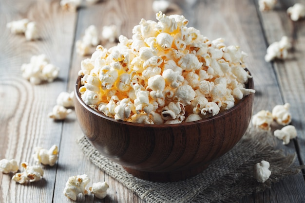A wooden bowl of salted popcorn at the old wooden table