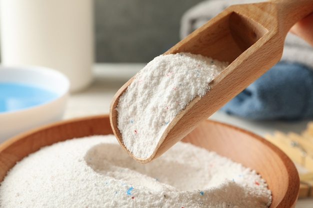 Wooden bowl and scoop with laundry powder, close up