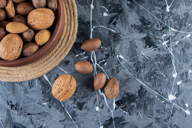 Wooden bowl of shelled various nuts on marble surface.