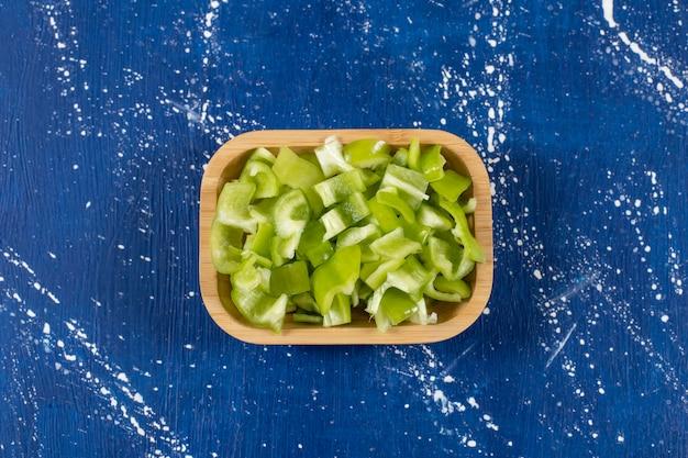 Ciotola di legno di peperoni verdi affettati su superficie di marmo.
