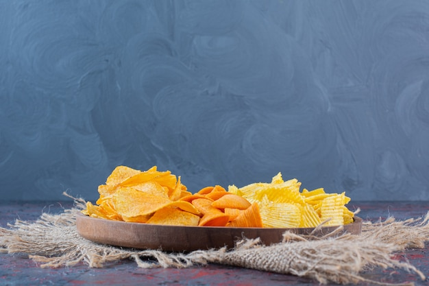 Wooden bowl of snacks for beer on a dark background.