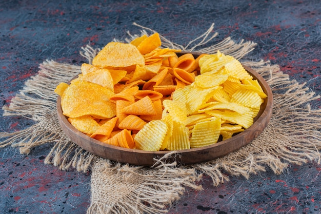 Wooden bowl of snacks for beer on a dark surface