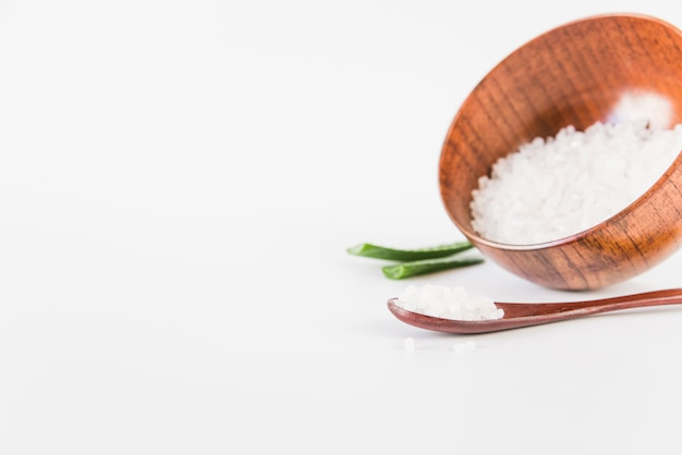 Wooden bowl and spoon with rock salt on white background