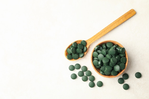 Wooden bowl and spoon with spirulina pills on white textured background