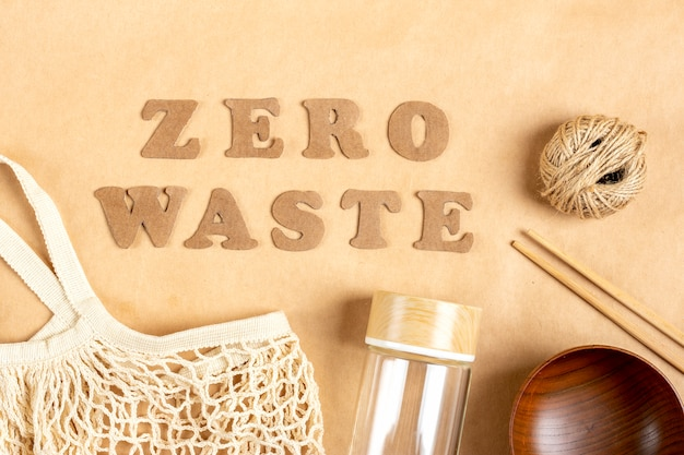 Wooden bowl, sticks, letters zero waste cut out of cardboard, woolen shopping mesh bag, glass bottle on of craft paper