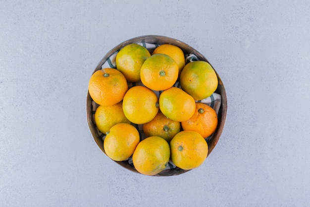 Wooden bowl of tangerines on marble background.