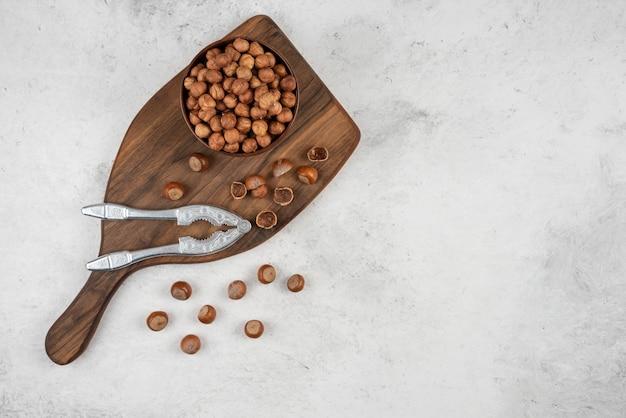 Ciotola di legno di noccioli di nocciola organici non pelati sul tagliere.