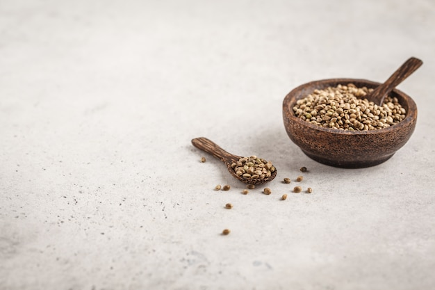 Wooden bowl of untreated hemp seeds. white background, copy space.
