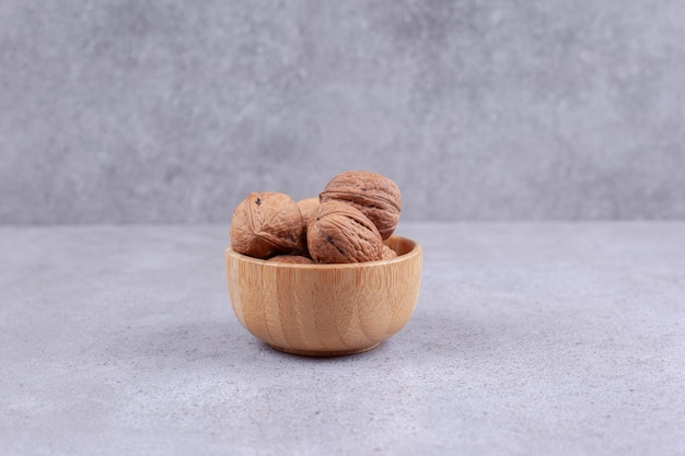 A wooden bowl of walnuts on marble background. high quality photo