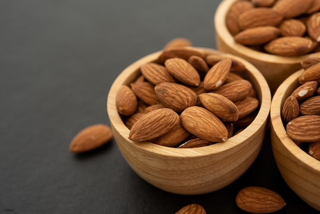 Wooden bowl with almond on black background. top view.