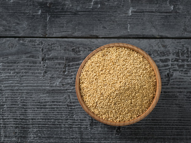 Wooden bowl with amaranth seeds on dark wooden table