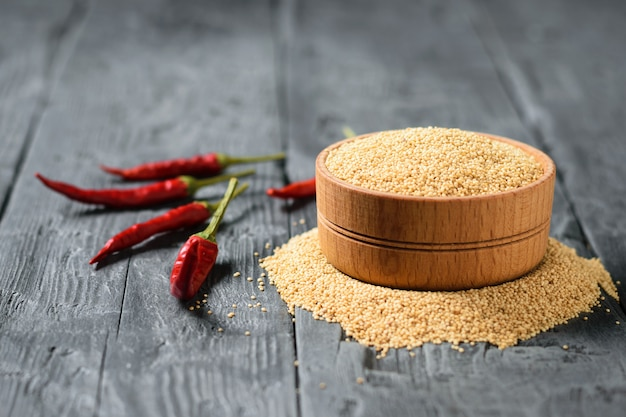 Wooden bowl with amaranth seeds and three chili pepper on dark wooden table.