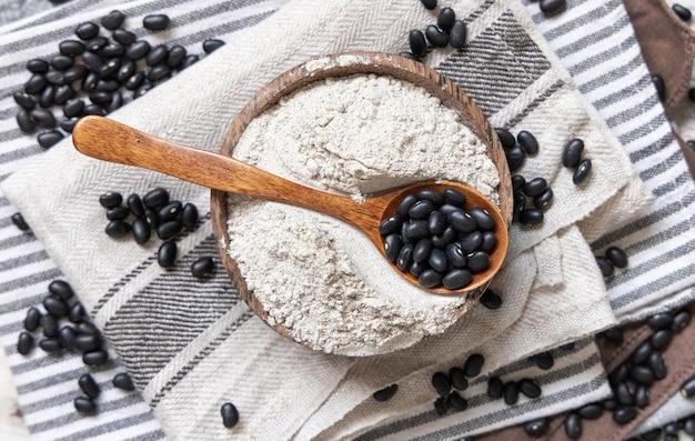 黒豆粉と木のスプーン上面図の乾燥豆と木製のボウル。健康的な食事と菜食主義の概念。伝統的なラテンアメリカのいとこ成分