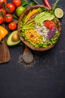 Wooden bowl with chickpea, avocado, wild rice, quinoa, bell pepper, tomatoes, greens, cabbage, lettuce on dark stone table and wooden spoon with chia seeds. top view with copyspace.