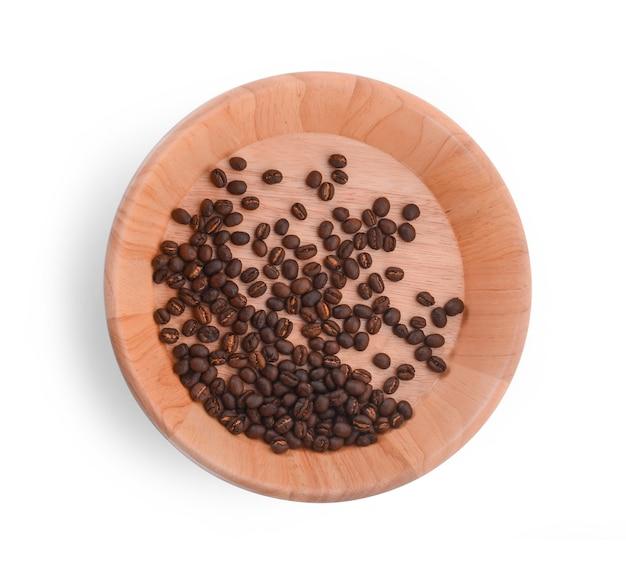 白い背景の上のコーヒー豆と木製のボウル。