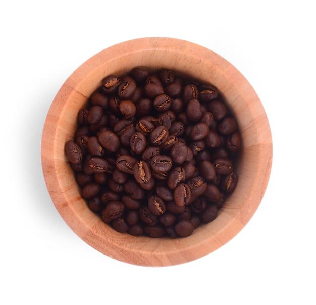 白い表面にコーヒー豆が入った木製のボウル。