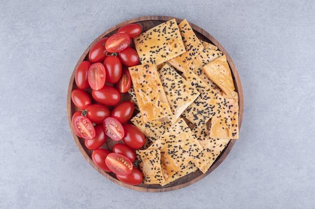 Ciotola di legno con cracker croccanti e pomodori su superficie in pietra