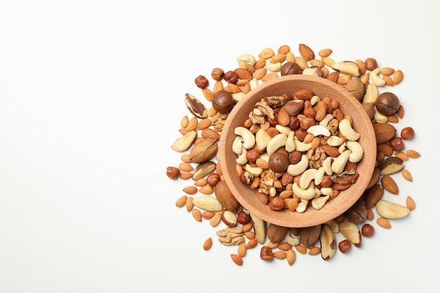 Wooden bowl with different tasty nuts on white background