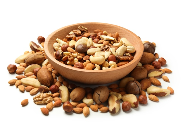 Wooden bowl with different tasty nuts on white