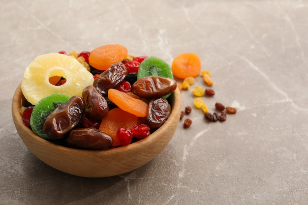 Wooden bowl with dried fruits on gray table
