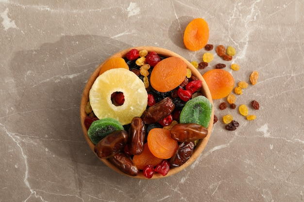 Wooden bowl with dried fruits on gray