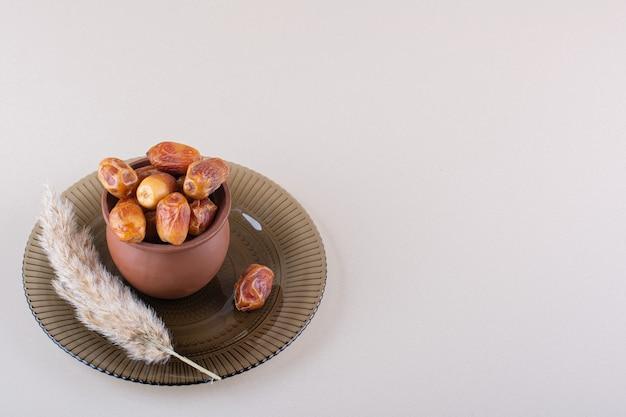 말린 맛있는 날짜가 있는 나무 그릇은 흰색 배경에 있습니다. 고품질 사진