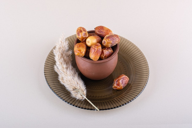말린 맛 있는 날짜가 있는 나무 그릇은 흰색 배경에 있습니다. 고품질 사진
