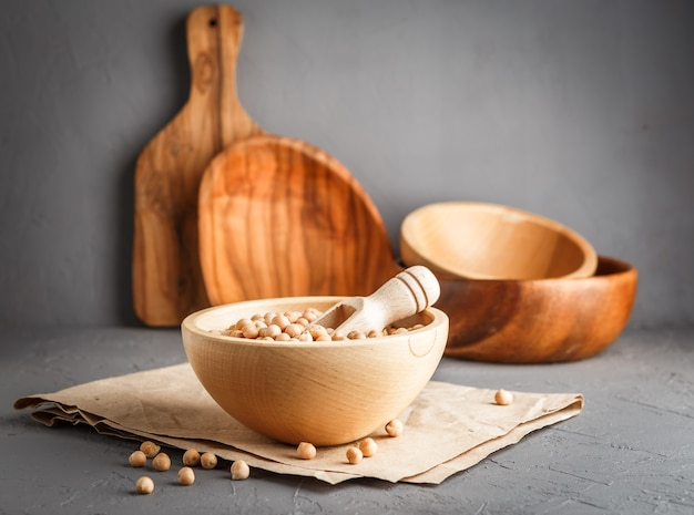 Wooden bowl with dry raw organic chickpeas on gray concrete background