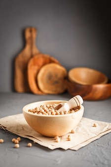 Wooden bowl with dry raw organic chickpeas on gray concrete