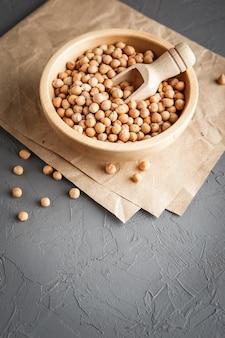 灰色のコンクリートの背景に乾燥生有機ひよこ豆と木製のボウル