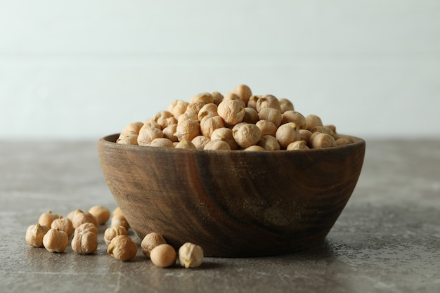 Wooden bowl with fresh chickpea on gray table